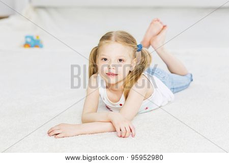 Cute happy girl lying on floor and dreaming