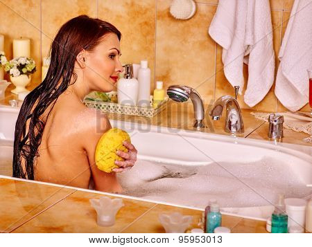Woman washing and relaxing at water in bubble bath.