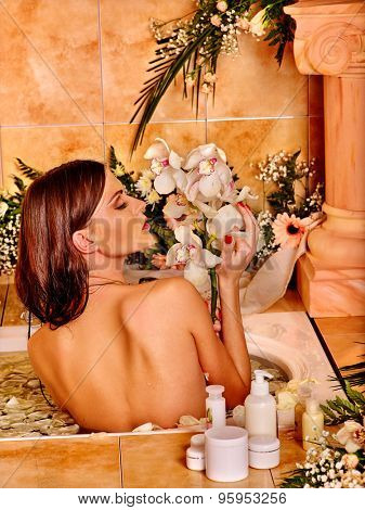 Woman with close up applying moisturizer at bathroom.