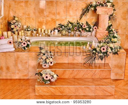 Home bathroom interior with bubble bath and flowers.