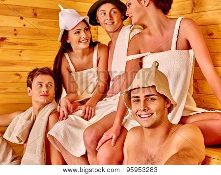 Group people of five in  hat  relaxing at sauna. Men and women.