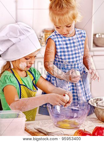 Children kid girls with rolling-pin dough at kitchen.