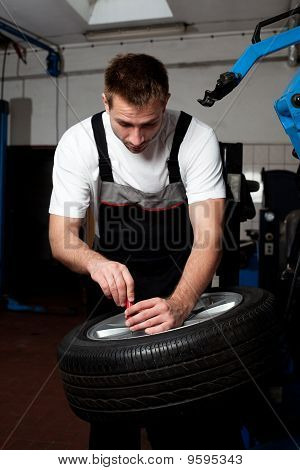 Mechanic Fixing Tyre In Car Service