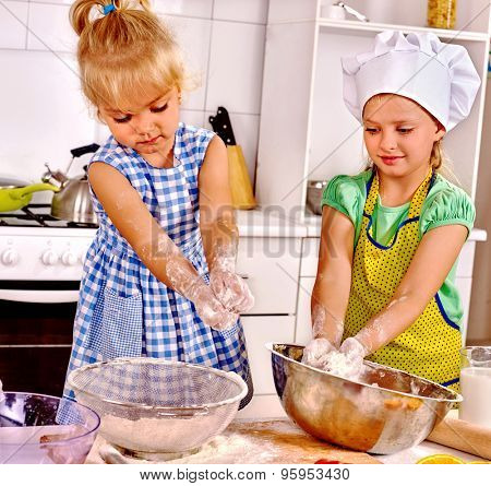 Girl kids  with rolling-pin dough at kitchen.