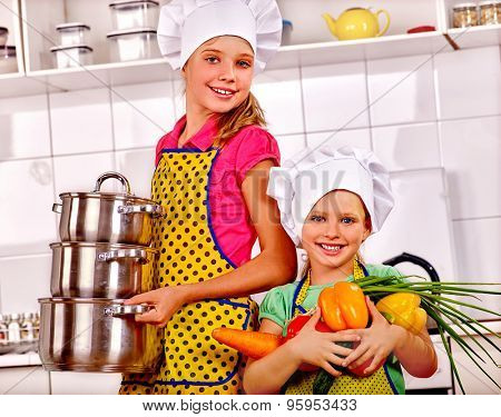 Kids in cooking hat holding a lot of vegetable at kitchen.