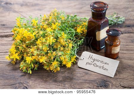 Hypericum perforatum and medicine bottles on wooden background