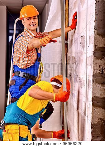 Two working men in builder uniform indoor.