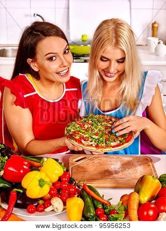 Two yong women cooking pizza at kitchen.