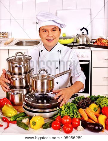 Happy man in chef hat holding pans cooking dinner.