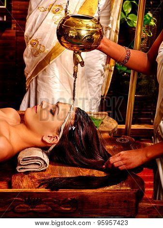 Young woman having pouring oil head Ayurveda spa treatment.