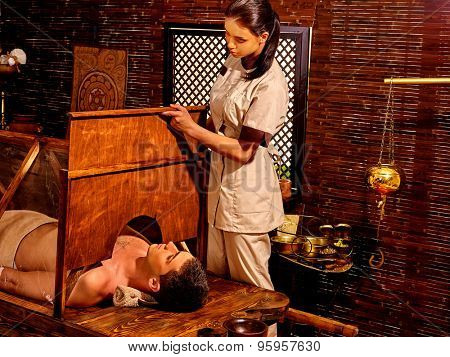 Man having Ayurvedic sauna treatment.