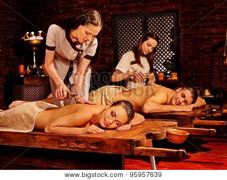 Couple  having oil Ayurveda spa treatment. Fours people indoor.