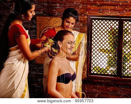 Young woman having ayurveda in Indian spa treatment.