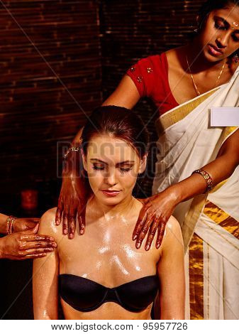 Young woman having neck and shoulders Ayurveda spa treatment.