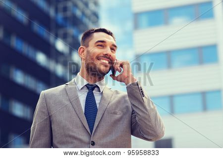 business, technology and people concept - smiling businessman with smartphone talking over office building