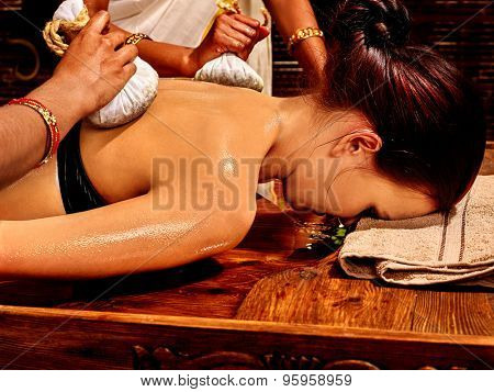 Woman having Ayurveda massage with pouch of rice. Not visible face.