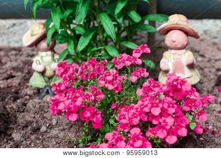 Flowerbed With Little Flowers And Garden Figurines