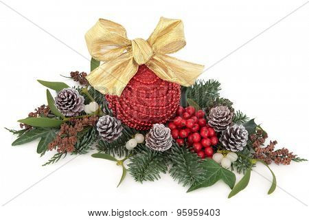 Christmas decoration with red bauble, holly, mistletoe, ivy and winter greenery over white background.
