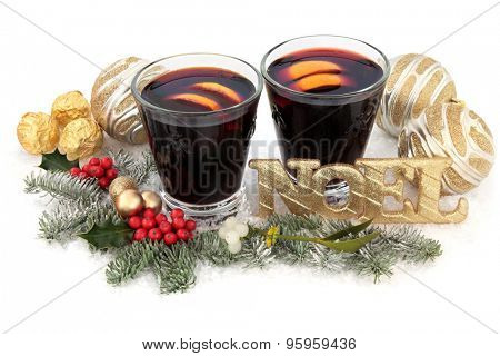 Christmas mulled wine with gold noel sign on snow with bauble decorations, holly, mistletoe and winter greenery over white background.