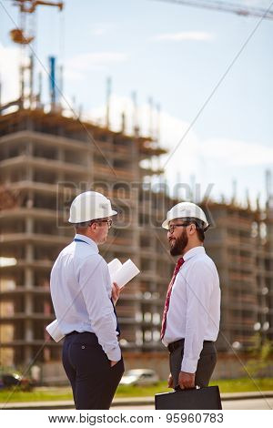 Modern businessmen in helmets interacting in front of unfinished construction