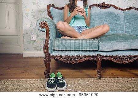 Woman looking smartphone sitting on sofa with legs crossed