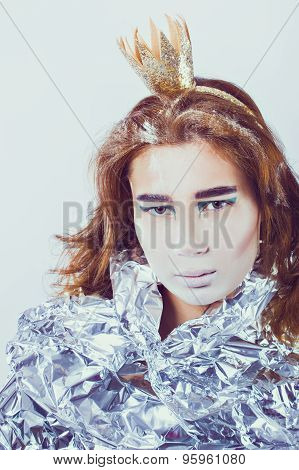 Portrait of pretty woman wrapped in foil with coronet looking forward standing on light grey backgro