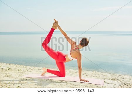 Sporty female in activewear doing exercise for stretching and keeping balance