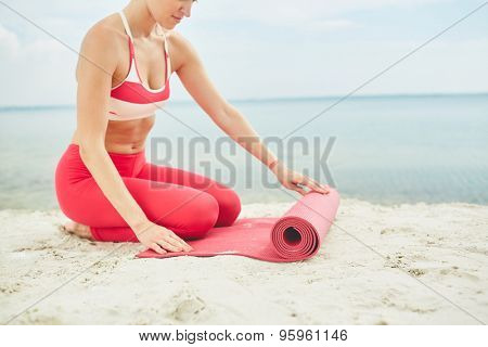 Fit woman unfolding mat before exercising on sandy beach