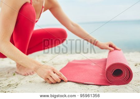Close-up of young woman unfolding mat for yoga practice