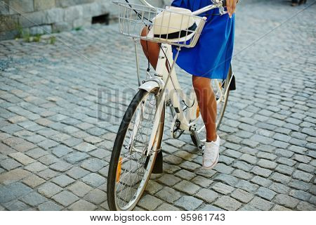 Young female in blue skirt riding bicycle in urban environment