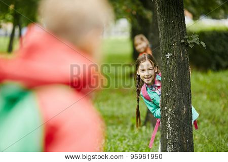 Little girl looking at camera out of tree trunk