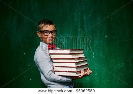 Cute schoolboy holding stack of books against blackboard