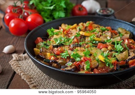 Vegetable Ratatouille in frying pan on a wooden table