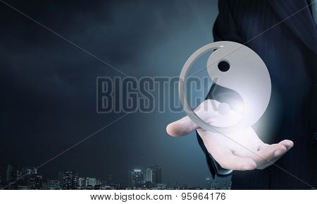 Close up of businessman holding ying yan symbol in palm