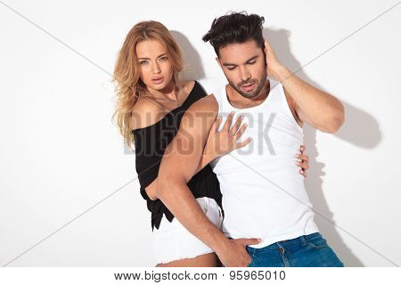 Blonde casual woman embracing her boyfriend while he is looking down.