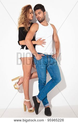 Side view of a tall sexy woman holding her lover while he is looking down.