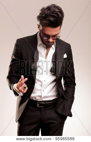 Elegant business man looking down with one hand in his pocket while snapping his fingers.
