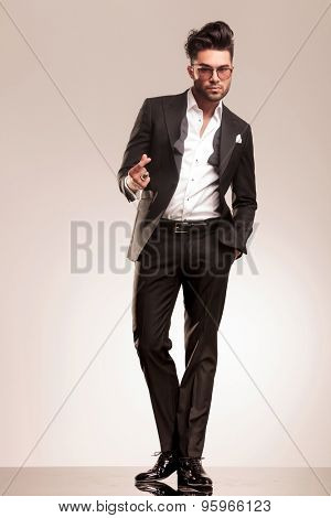 Full body image of a young handsome business man holding one hand in his pocket while snapping his fingers.