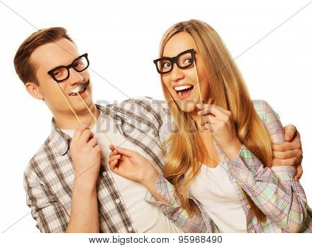 people, friendship, love and leisure concept - lovely couple holding party glasses on stick