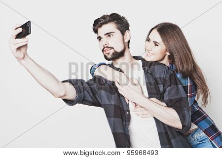 Capturing happy moments together. Happy young loving couple making selfie and smiling while standing against white background.Special Fashionable toning.