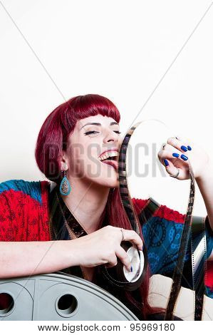 Young Woman Smile Behind Big Movie Cinema Reel Licking Filmstrip