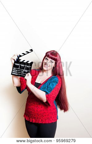Young Woman Smiling Showing Movie Clapper Board