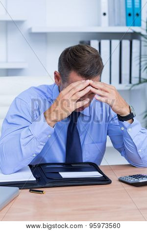 Elegant businessman with severe headache sitting at office desk