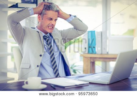 Furious businessman looking at laptop computer in office