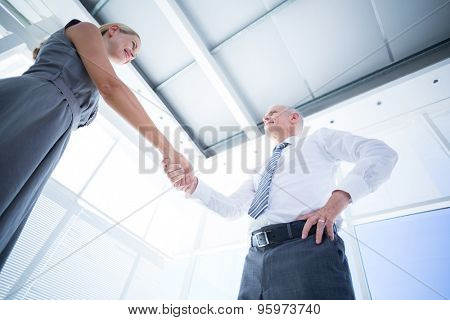 Low angle view of two smiling business people shaking hands