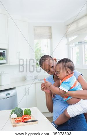 Happy smiling mother with babyboy son in the kitchen