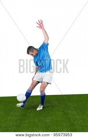 Determined rugby player kicking a rugby ball