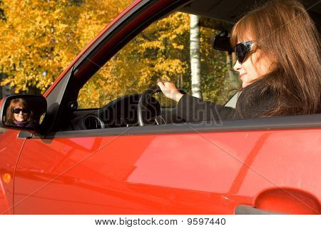 The Girl In The Red Car And Her Reflection In A Mirror