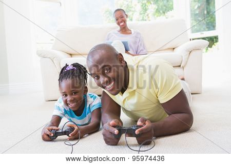 Portrait of a happy smiling father playing with her daughter at video games in living room