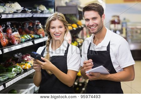 Portrait of a colleagues looking at notebook together at supermarket